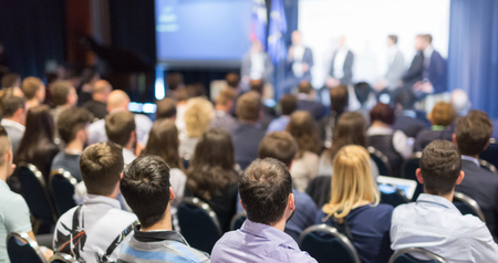Round table discussion at business and entrepreneurship symposium. Audience in conference hall. Lens focus on unrecognized participant in rear of audience. Stock Photo
