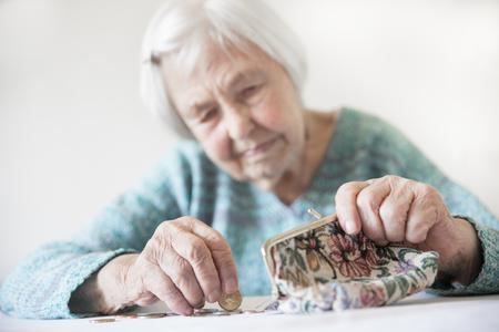 Ältere 96-jährige Frau, die zu Hause kläglich am Tisch sitzt und nach dem Bezahlen von Rechnungen Restmünzen aus der Rente in ihrer Brieftasche zählt. Unhaltbarkeit der Sozialtransfers und des Rentensystems.