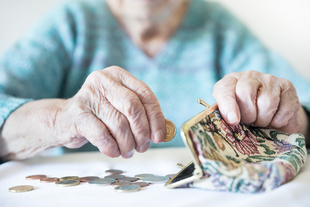 Detailed closeup photo of elderly 96 years old womans hands counting remaining coins from pension in her wallet after paying bills. Unsustainability of social transfers and pension system. Stock Photo