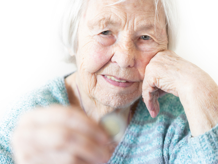 Portrait of sad elderly woman sitting at table at home and looking miserably at only remaining coin from pension in hand. Unsustainability of social transfers and pension system. Selective focus. Stock Photo