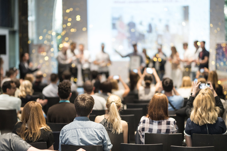 Young business team receiving award prize at best business project competition event. Business and entrepreneurship award ceremony theme. Focus on unrecognizable people in audience. Stock Photo