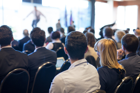 Motivational speaker giving a talk in conference hall at business event. Audience at the conference hall. Business and Entrepreneurship concept. Focus on unrecognizable people in audience. Stock Photo