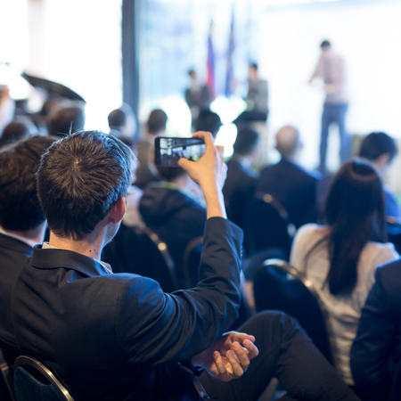 Businessman takes a picture of corporate business presentation at conference hall using smartphone. Business and Entrepreneurship concept. Focus on unrecognizable person in audience.