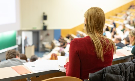 Female student attending faculty lecture workshop making notes. Audience at the lecture hall. Conference and Presentation. Business and entrepreneurship academic education concept.