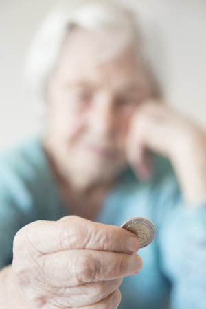 Sad elderly woman sitting at the table at home and looking miserably at only remaining coin from pension in her hand. Unsustainability of social transfers and pension system. Focus on coin. Stock Photo
