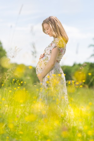 Portrait of beautiful pregnant woman in white summer dress relaxing in meadow full of yellow blooming flovers. Concept of healthy maternity care.