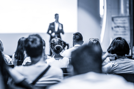 Speaker giving talk at business event. Audience at the conference hall. Business and Entrepreneurship concept. Focus on unrecognizable people in audience. Blue toned grayscale image. Stock Photo