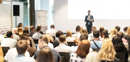 Male speaker giving a talk in conference hall at business event. Audience at the conference hall. Business and Entrepreneurship concept. Focus on unrecognizable people in audience. Stock Photo