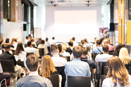 Talk in conference hall at business event. Audience at the conference hall. Business and Entrepreneurship concept. Focus on unrecognizable people in audience. Copy space on empty white screen. Stock Photo