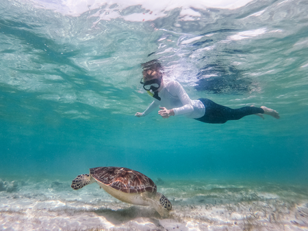 Woman wearing snokeling mask swimming with sea turtle in turquoise blue water of Gili islands, Indonesia. Underwater photo. Hawksbill sea turtle, Eretmochelys imbricata is endangered species.