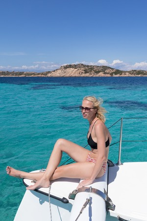 Woman in bikini tanning and relaxing on a summer sailin cruise, sitting on a luxury catamaran near picture perfect white sandy beach on Spargi island in Maddalena Archipelago, Sardinia, Italy. 写真素材