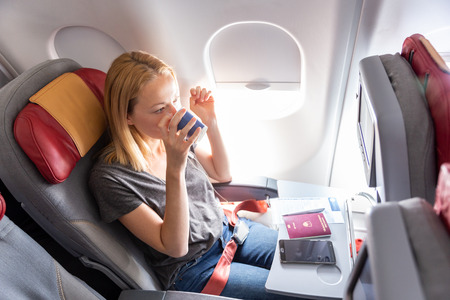 Woman on commercial passengers airplane during flight. Female traveler seated in passanger cabin drinking coffee. Sun shining trough airplane window. Фото со стока