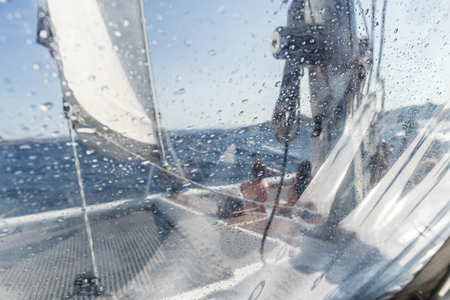 Sailing yacht catamaran sailing in rough sea. Sailing. Sailboat concept. Narrow depth of field image focused on water drops on splash protective canvas. Reklamní fotografie