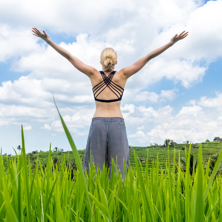 Relaxed woman, arms rised, enjoying pure nature at beautiful green rice fields on Bali. Concept of nature enjoyment, balanced life, freedom, vacations, happiness, and well being.