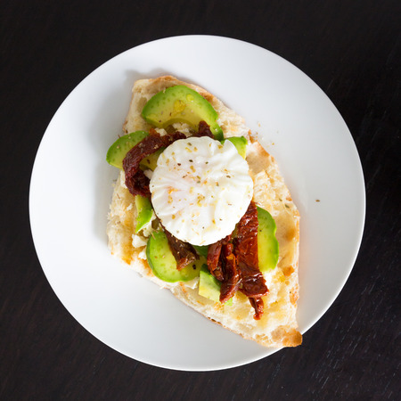 Poached egg on a toasted bun with avocados and dried tomatoes on white plate.