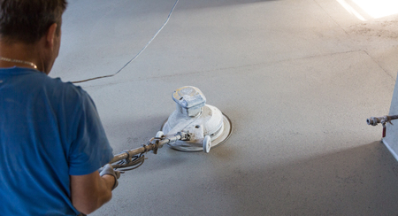 Laborer performing and polishing sand and cement screed floor. Sand and cement floor screed.