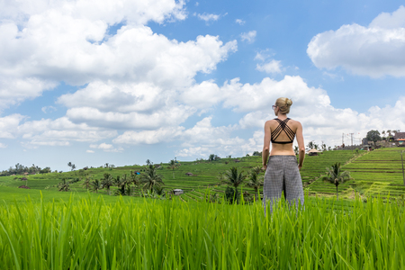 Relaxed sporty female traveler enjoying pure nature at beautiful Jatiluwih rice fields on Bali. Concept of sustainable tourism, nature enjoyment, balanced life, freedom, vacations and well being. Stock Photo
