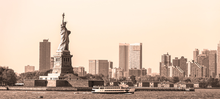 Statue of Liberty with Liberty State Park and Jersey City skyscrapers in background, USA. Black and white yellow toned image. 写真素材