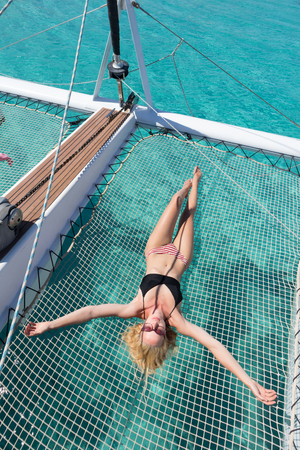 Womanin bikini tanning and relaxing on a summer sailin cruise, lying in hammock of luxury catamaran near picture perfect white sandy beach on Spargi island in Maddalena Archipelago, Sardinia, Italy. 写真素材