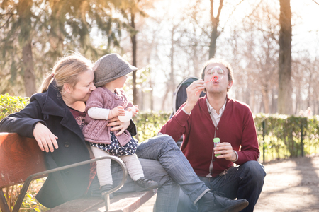 Young happy family with cheerful child having fun in park on sunny day. Father blowing soap bubbles.