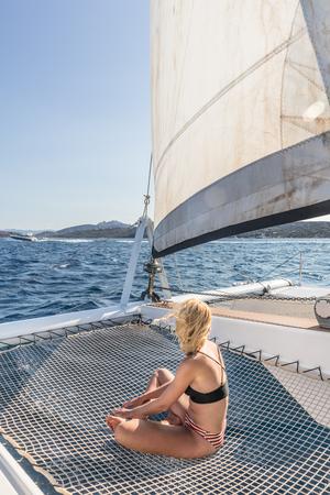 Schöne Frau, die sich auf einer Segelkreuzfahrt im Sommer entspannt, sich in der Hängematte eines Luxus-Katamaran-Segelns rund um den Maddalena-Archipel, Sardinien, Italien im warmen Nachmittagslicht entspannt und sonnen kann.