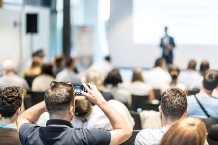 Business and entrepreneurship symposium. Speaker giving a talk at business meeting. Audience in conference hall. Rear view of unrecognized participant in audience taking photo of presentation. Stock Photo
