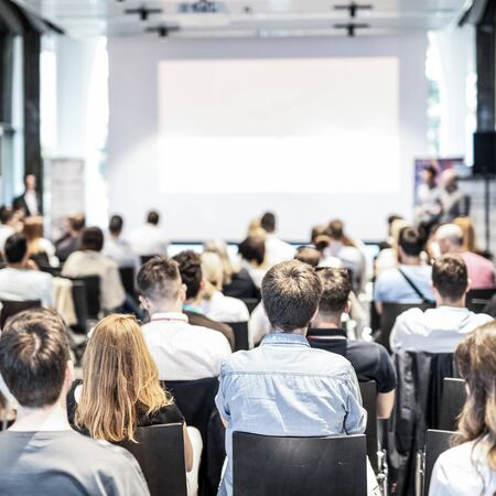 Audience at the conference hall. Copy space on the white screen. Talk at business conference event. Business and Entrepreneurship concept. Focus on unrecognizable people in audience. Stock Photo