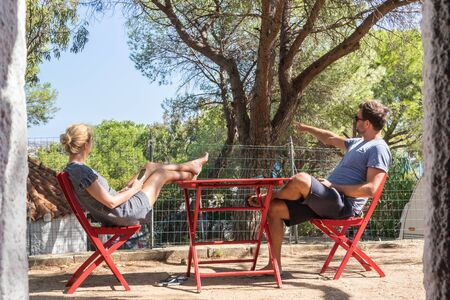 Couple on vacations resting and enjoing in front of mobile home house at camping site in pure nature. Family vacation travel, holiday trip Sardigna, Italy. Reklamní fotografie