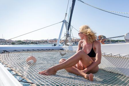 Beautiful woman relaxing on a summer sailing cruise, sitting and sunbathing in hammock of luxury catamaran sailing around Maddalena Archipelago, Sardinia, Italy in warm afternoon light. 写真素材
