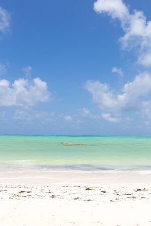 Solitary fishing boat on picture perfect white sandy beach with turquoise blue sea, Paje, Zanzibar, Tanzania. Copy space.