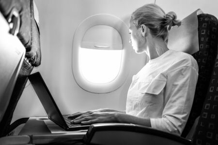 Attractive caucasian female passenger looking through the plain window while working on modern laptop computer using wireless connection on board of commercial flight. Black and white image. 写真素材