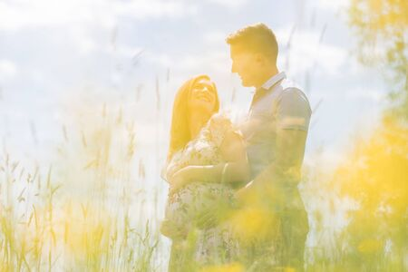 Young happy pregnant couple hugging in nature. Concept of love, relationship, care, marriage, family creation, pregnancy, parenting
