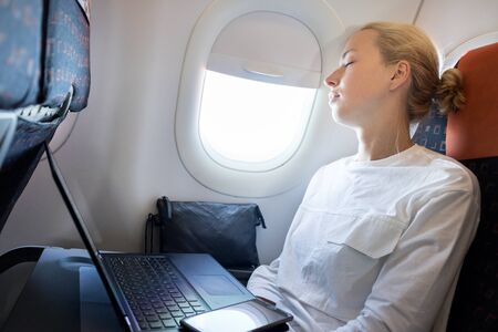 Tired business woman napping on airplane during her business trip woking tasks. Female passenger in flying aircraft sleeps next to the window.