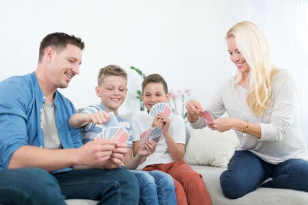 Happy young family playing card game on living room sofa at home. Spending quality leisure time with children and family concept. Cards are generic and debranded.