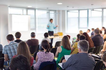 Symposium für Wirtschaft und Unternehmertum. Sprecher, der ein Gespräch beim Geschäftstreffen gibt. Publikum im Konferenzsaal. Rückansicht eines unbekannten Teilnehmers am Publikum.