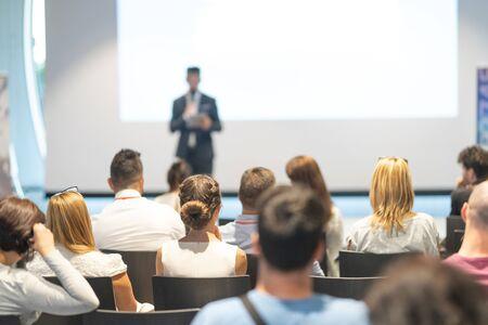 Männlicher Sprecher, der einen Vortrag im Konferenzsaal bei einer Geschäftsveranstaltung hält. Publikum im Konferenzsaal. Geschäfts- und Unternehmerkonzept. Konzentrieren Sie sich auf nicht erkennbare Personen im Publikum. Standard-Bild