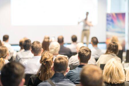 Sympozjum biznesu i przedsiębiorczości. Prelegent wygłaszający przemówienie na spotkaniu biznesowym. Publiczność w sali konferencyjnej. Widok z tyłu nierozpoznanego uczestnika na widowni.