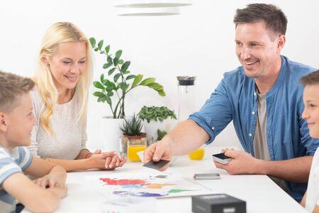 Gelukkig jong gezin speelkaartspel aan eettafel in lichte moderne woning. Kwaliteitsvrije tijd doorbrengen met kinderen en familieconcept. Kaarten zijn generiek en merkloos.