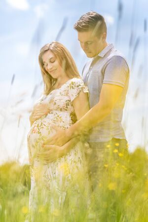 Joven pareja feliz embarazada abrazándose en la naturaleza. Concepto de amor, relación, cuidado, matrimonio, creación de familia, embarazo, crianza de los hijos Foto de archivo