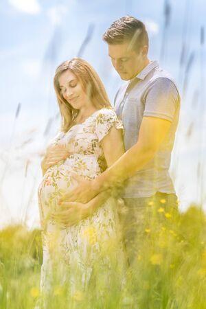 Junge glückliche schwangere Paare, die in der Natur umarmen. Konzept der Liebe, Beziehung, Fürsorge, Ehe, Familiengründung, Schwangerschaft, Elternschaft Standard-Bild