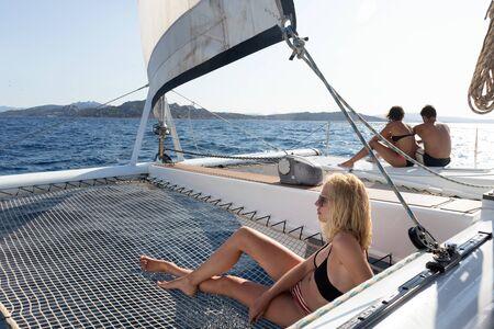 Beautiful woman relaxing on a summer sailing cruise, lying and sunbathing in hammock of luxury catamaran sailing around Maddalena Archipelago, Sardinia, Italy in warm afternoon light.