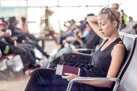 Voyageuse blonde décontractée et bronzée tenant un téléphone portable, un passeport et une carte d'embarquement en attendant de monter à bord d'un avion aux portes d'embarquement du terminal de l'aéroport asiatique.