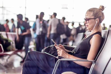 Casual sporty young blond female traveler using her cell phone while waiting to board a plane at the departure gates at the asian airport terminal.