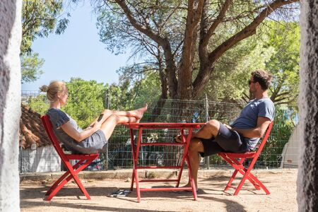 Couple on vacations resting and enjoing in front of mobile home house at camping site in pure nature. Family vacation travel, holiday trip Sardigna, Italy. Stock Photo - 127128801
