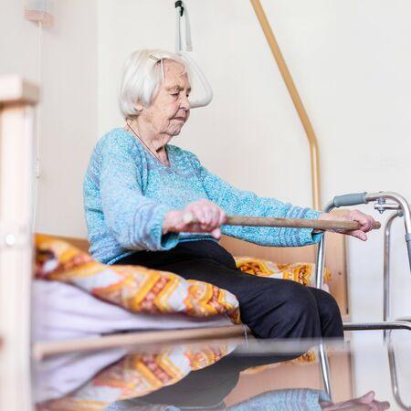 Femme âgée de 96 ans exerçant avec un bâton assis sur son mauvais. Concept de soutien à domicile en soins de santé gériatrique pour les personnes âgées. Soins aux personnes âgées. Banque d'images