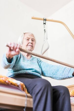 Elderly 96 years old woman exercising with a stick sitting on her bad. Geriatric health care home assisted support for older people concept. Care for the elderly. Foto de archivo