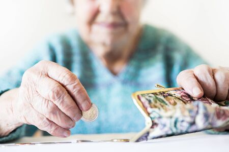 Detailed closeup photo of elderly 96 years old womans hands counting remaining coins from pension in her wallet after paying bills. Unsustainability of social transfers and pension system. Banco de Imagens