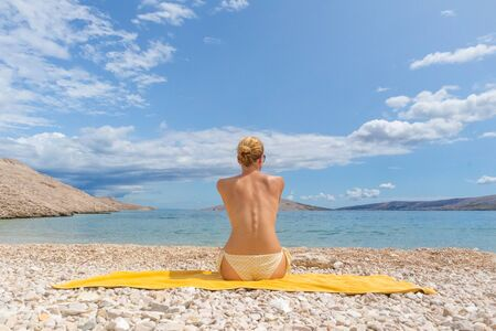Rear view of relaxed sexy young caucasian woman sitting on yellow towel, sunbathing topless alone on romote pabble beach on Pag island, Croatia, Mediterranean. Enjoying pure nature. 写真素材