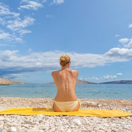 Rear view of relaxed young caucasian woman sitting on yellow towel, sunbathing alone on romote pabble beach on Pag island, Croatia, Mediterranean. Enjoying pure nature.