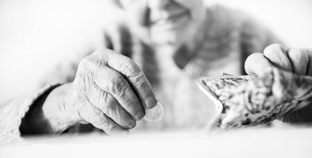 Closeup photo of elderly 96 years old womans hands counting remaining coins from pension in wallet after paying bills. Unsustainability of social transfers and pension system. Black and white.